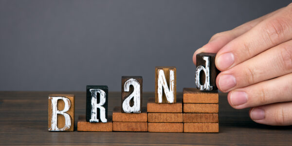 BRAND. Design, marketing, management and success concept. Wooden alphabet letters on steps. Gray background